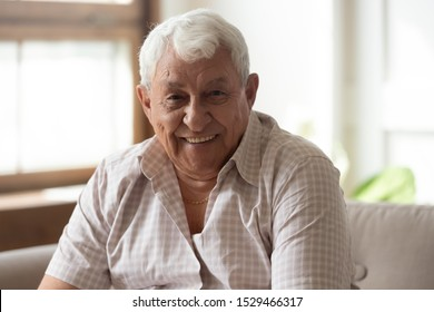 Elderly positive happy man seated on couch in living room smiles looking at camera feels healthy, 80s grandfather having wide toothy smile, concept of dental care exam for senior clinic advertisement