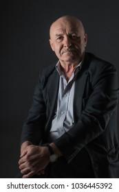 Elderly positive male businessman on a dark background