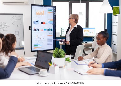 Elderly project manager pointing at desktop presenting statistical data, briefing diverse group of employees. Multiethnical businesspeople working in professional startup financial office during