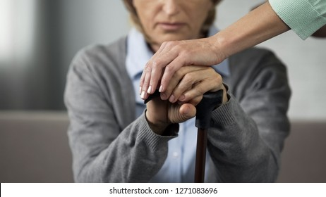 Elderly retired lady sitting on sofa, young woman touching her hands carefully