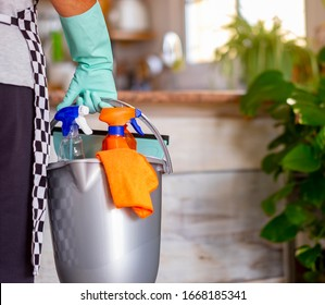 Elderly retired woman busy with house hygiene works holding a bucket full of cleaning products - precautions against virus infection
