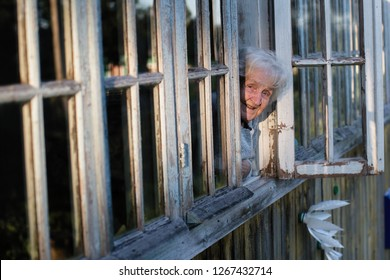 Elderly russian woman looks from window of a village house.