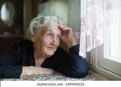 Elderly russian woman sits in a house near the window.