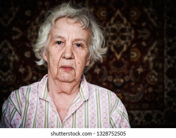 Elderly sad gray-haired woman. Real people