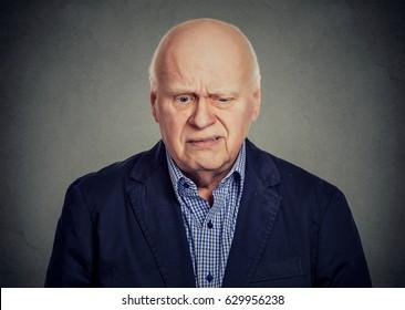 Elderly sad skeptical man looking down