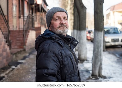 Elderly sad tired man on a city street in winter, real people every day life