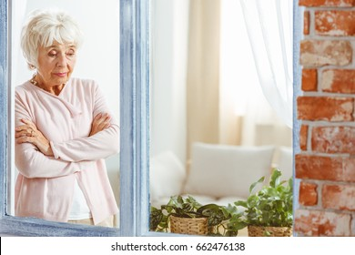 Elderly sad woman looking down wondering by the window