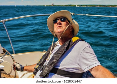 An elderly seafarer manages a sailing boat on a sunny summer day. A senior citizen is wearing a life jacket.