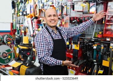Elderly seller posing near electric compressor in household store