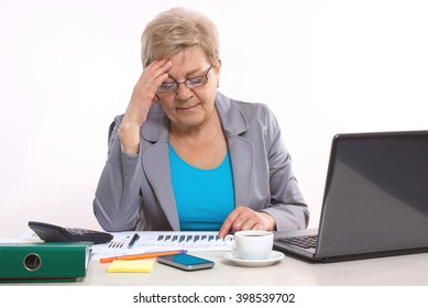 Elderly senior business woman holding hand on her head and working at desk in office, analyzing financial charts, business concept, analysis of sales plan, business report