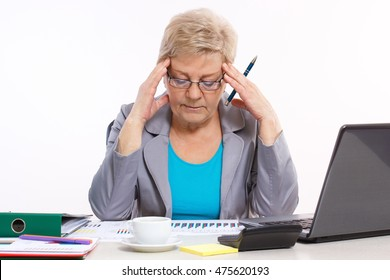 Elderly senior business woman holding hand on her head and analyzing financial charts at desk in office, analysis of sales plan