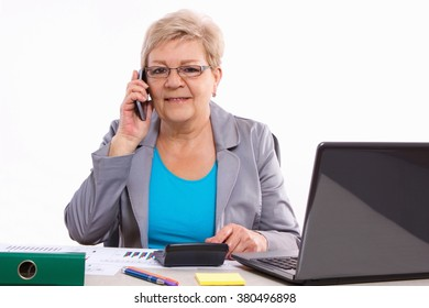 Elderly senior business woman talking on mobile phone and working with calculator and financial charts at her desk in office, business concept, analysis of sales plan, business report