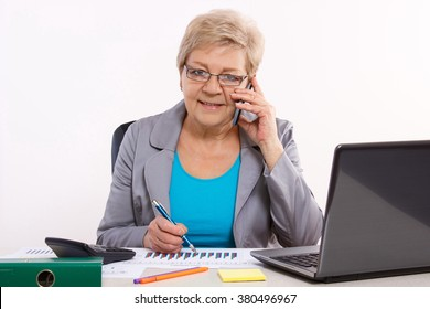 Elderly senior business woman talking on mobile phone and working with laptop and financial charts at her desk in office, business concept, analysis of sales plan, business report