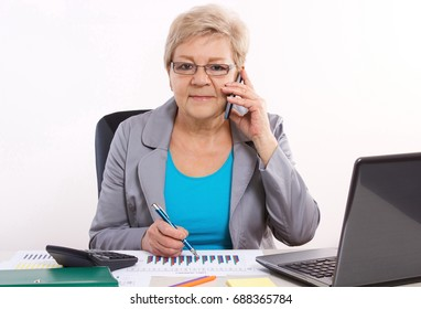 Elderly senior business woman talking on mobile phone and working with laptop and financial charts at her desk in office