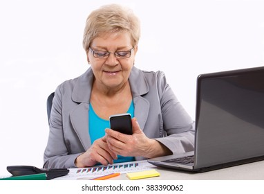 Elderly senior business woman using mobile phone and working with financial charts at her desk in office, business concept, analysis of sales plan, business report