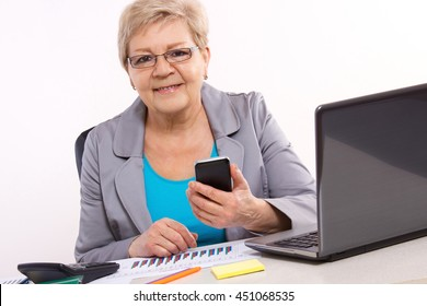 Elderly senior business woman using mobile phone and working with financial charts at desk in office, analysis of sales plan