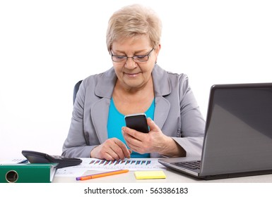 Elderly senior business woman using mobile phone and working with financial charts at her desk in office, analysis of sales plan
