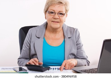 Elderly senior business woman working with calculator, laptop and financial chart at her desk in office, business concept, analysis of sales plan, business report