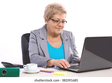 Elderly senior business woman working with laptop and financial chart at her desk in office, business concept, analysis of sales plan, business report