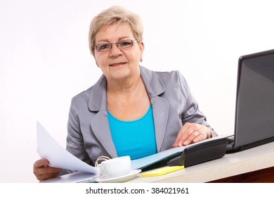 Elderly senior business woman working with documents and financial chart at her desk in office, analysis of sales plan, business report
