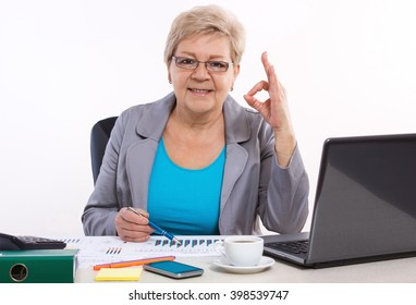 Elderly senior business woman working at her desk in office, analyzing financial charts and showing sign ok, business concept, analysis of sales plan, business report