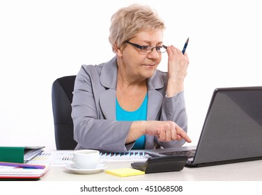 Elderly senior business woman working with laptop and financial chart at desk in office, analysis of sales plan