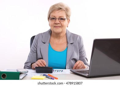 Elderly senior business woman working with calculator, laptop and financial chart at her desk in office, analysis of sales plan