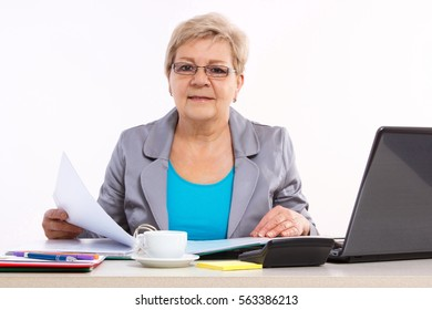 Elderly senior business woman working with documents and financial chart at her desk in office, analysis of sales plan