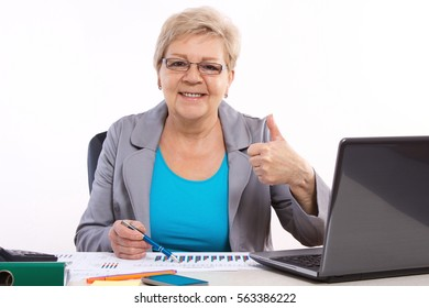 Elderly senior business woman working at her desk in office, analyzing financial charts and showing thumbs up, analysis of sales plan