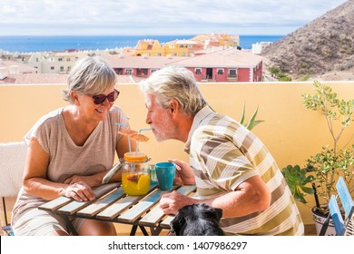 elderly senior couple man and woman with nice dog pug on the terrace. drink together from the same vase a fruit juice for healthy lifestyle. summer nice time of vacation in a terrace and ocean view