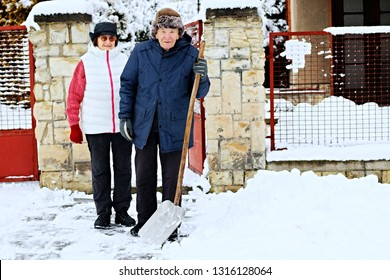 Elderly senior couple standing in front of his house holding a snow shovel. Leisure activities, spending time, happy retirement and senior lifestyle concept.