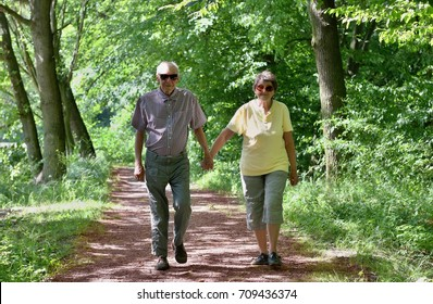 Elderly senior couple walking hand in hand in the nature. Concept of active elderly people during retirement. Everyday joy lifestyle without age limitation.