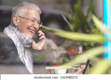Elderly senior lady talking on the phone in the cafe, view from the window