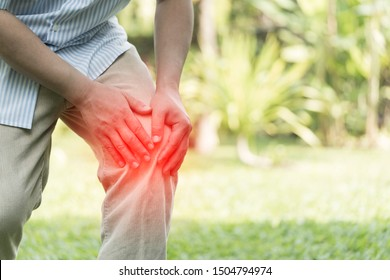 Elderly or Senior man hands hold on his knee or suffering from pain in knee while exercise at backyard. Injury, Knee pain, man with legs ache concept. Shot in morning time. highlight red effect