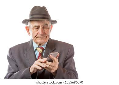 Elderly senior man in retro hat using his mobile phone isolated on white background