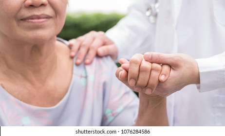 Elderly senior patient (aging old adult person) in nursing hospice home holding geriatrician doctor's hand having happy medical health care from hospital carer or caregiver healthcare service