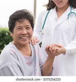 Elderly senior patient (Asian old aging person) in nursing hospice home holding geriatrician doctor's hand having happy health check-up medical care from hospital carer or caregiver healthcare service