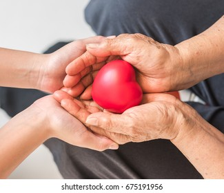 Elderly senior person or grand parent's hands with red heart  in support of nursing family caregiver for disability awareness day, national care giver month concept