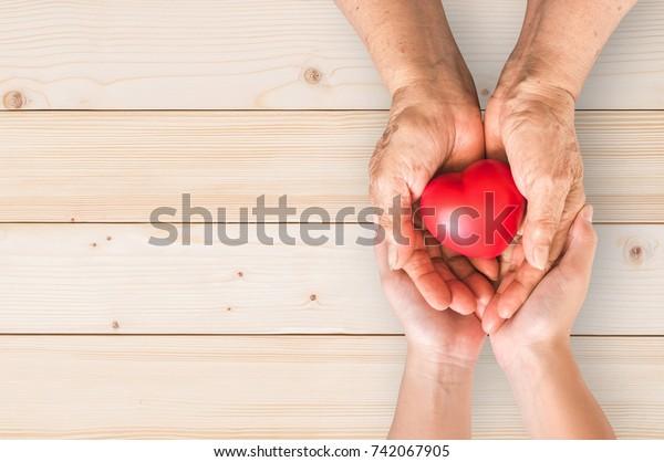 Ältere ältere Senioren oder Großeltern mit rotem Herzen zur Unterstützung der Pflegefamilienbetreuung für die Pflege der nationalen Krankenhäuser Palliativpflege und Familienbetreuer Monatskonzept
