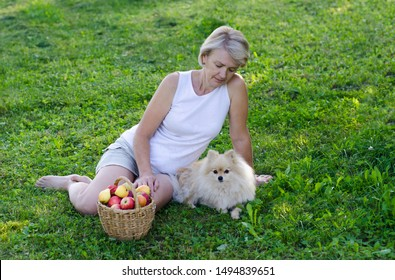 Elderly senior retired person, woman relaxing in the garden or in park. Mature adult female lying on the grass with pomeranian spitz dog or puppy with a basket of fruits, apples. Summer picnic outdoor