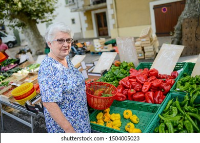 elderly senior woman buying fresh vegetables and fruits in farmer's market during a summer day in provence france