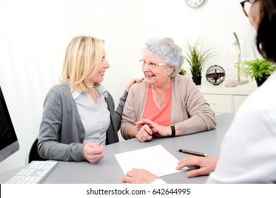 elderly senior woman with daughter signature legacy heritage testament document in a lawyer notary office
