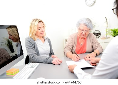 elderly senior woman with daughter signature legacy inheritance heritage testament document in a lawyer notary office