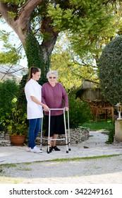 elderly senior woman with nurse walking outdoor in nursing home hospital garden