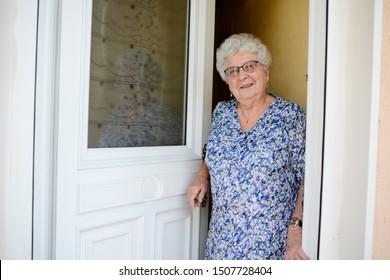 ältere ältere ältere ältere Frau, die Haustür öffnet und zu Hause Menschen empfängt