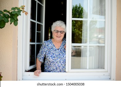 elderly senior woman opening a window of her house and welcoming people at home