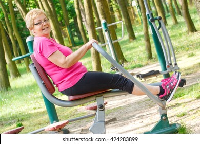 Elderly senior woman in sports wear exercising upper and lower body on outdoor gym in sunny park, trainer machine, healthy, sporty lifestyles and slimming concept