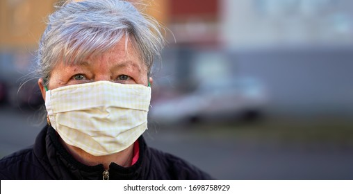 Elderly senior woman wearing home made cloth face mouth nose virus mask outside, blurred building background. Can be used during coronavirus covid-19 outbreak prevention