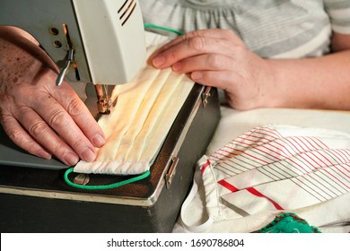 Elderly senior woman working on old sewing machine - making home made face masks against coronavirus spreading, closeup on finished mask