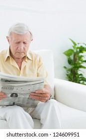 Elderly serious man reading newspapers on a sofa